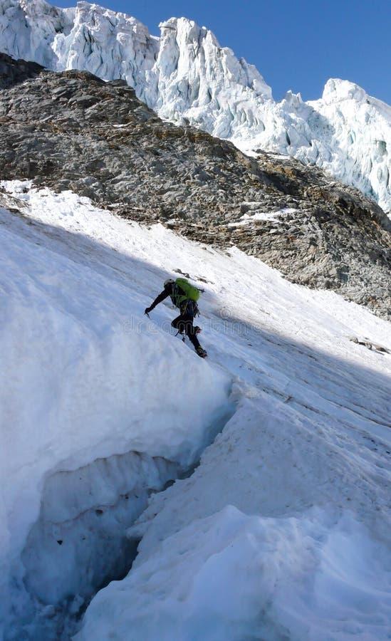 El escalador de montaña cruza encima una hendidura o un bergschrund grande y profunda mientras que él comienza su subida de una c imagen de archivo libre de regalías