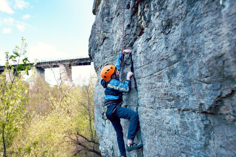 El escalador de roca del niño sube el acantilado fotografía de archivo libre de regalías