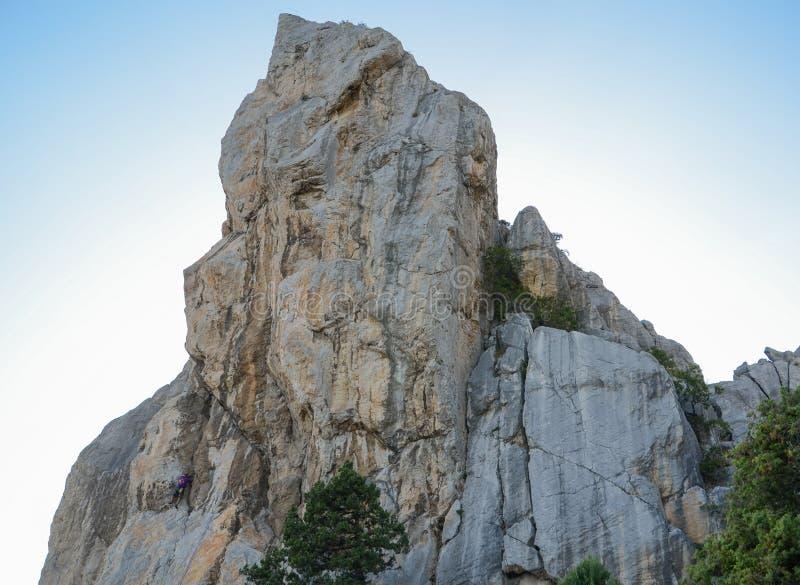 El escalador de roca sube al top de una montaña en la puesta del sol en Crimea imágenes de archivo libres de regalías