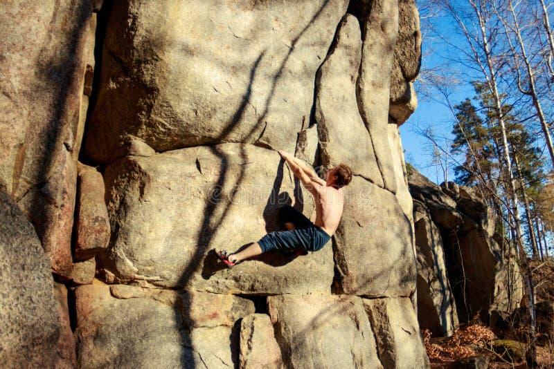 El escalador de roca sube un canto rodado sobre una roca sin seguro fotografía de archivo