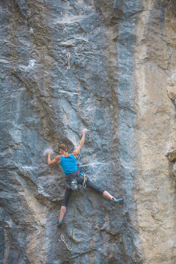 El escalador está entrenando para subir la roca imagenes de archivo