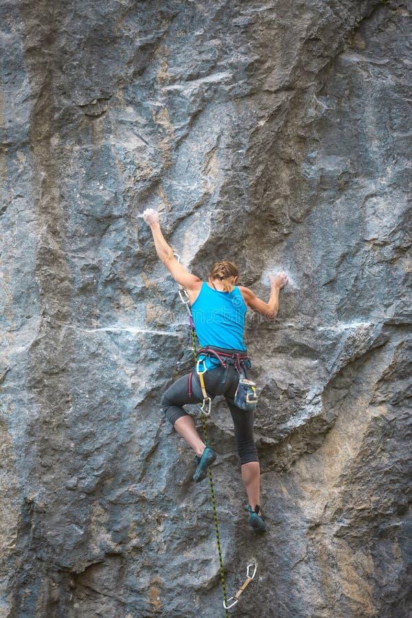 El escalador está entrenando para subir la roca imagen de archivo libre de regalías