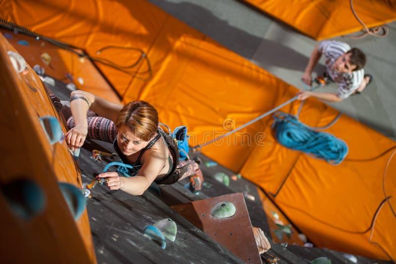 El escalador femenino está subiendo para arriba en la pared interior de la escalada foto de archivo