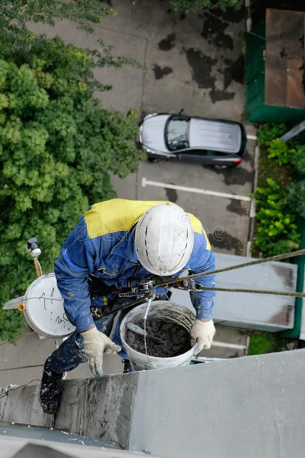 El escalador industrial repara la fachada de una casa en una altura con el equipo que sube imágenes de archivo libres de regalías