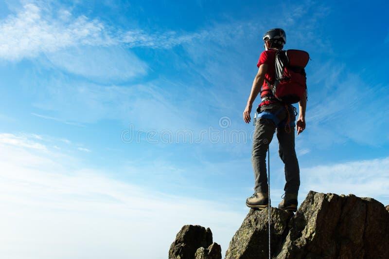 El escalador llega en la cumbre de un pico de montaña Conceptos: victo imagen de archivo