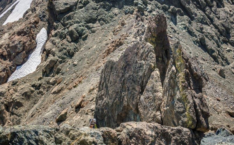 El escalador Rappels en Rocky Terrain imagen de archivo libre de regalías