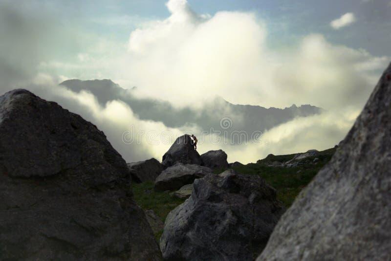 El escalador sube en las rocas en la distancia foto de archivo libre de regalías
