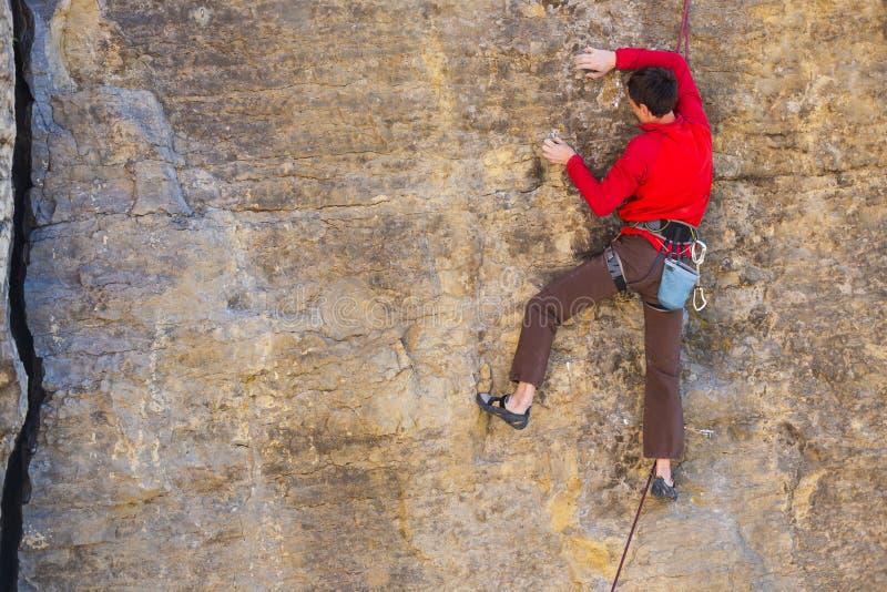 El escalador sube la roca fotografía de archivo