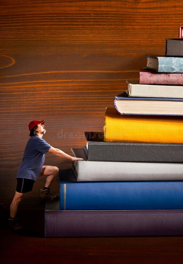 El escalador sube un montón de libros imágenes de archivo libres de regalías