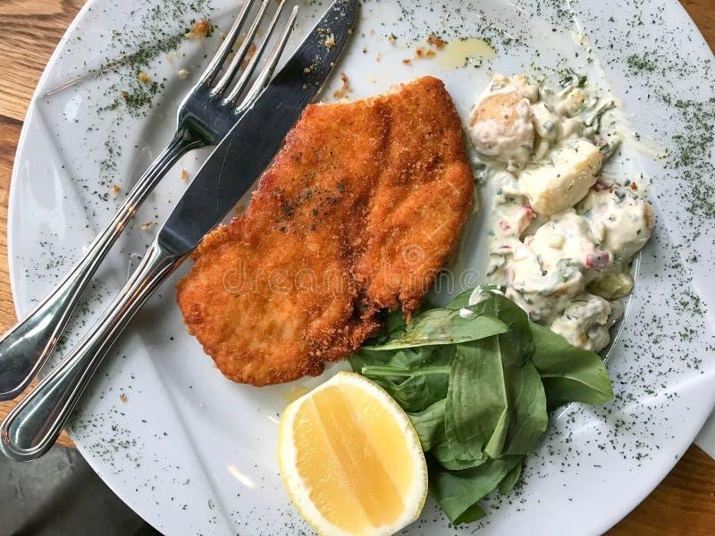 El escalope del pollo con la ensalada y el limón de patata sirvió en el restaurante foto de archivo libre de regalías