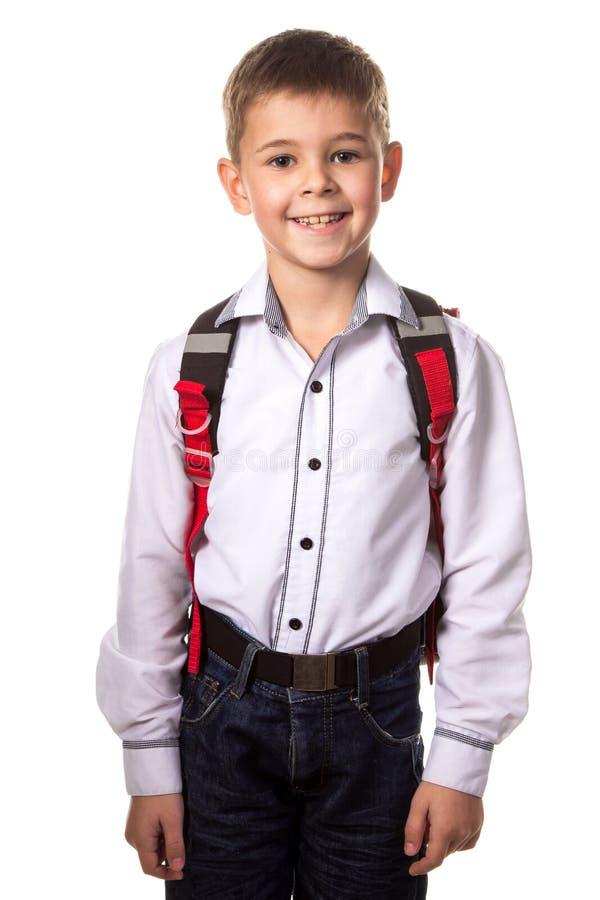 El escolar sonriente con la mochila, alista a la escuela en el fondo blanco fotografía de archivo