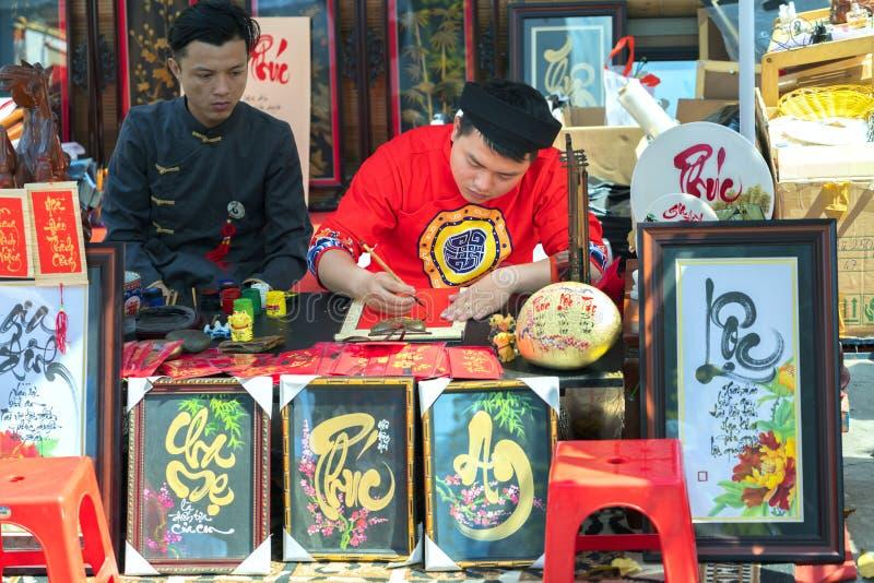 El escolar vietnamita escribe caligrafía en el festival lunar de la caligrafía del Año Nuevo foto de archivo