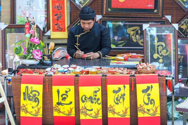 El escolar vietnamita escribe caligrafía en el festival lunar de la caligrafía del Año Nuevo imagenes de archivo