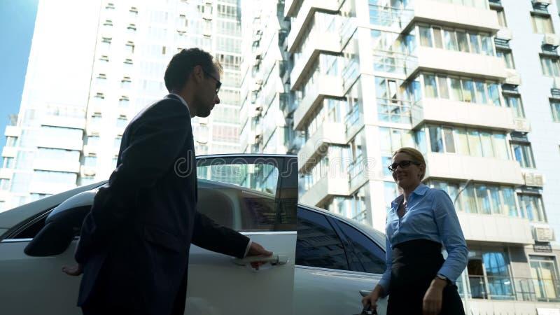 El escolta personal abre puertas de coche en la señora, seguridad para el político, celebridad imágenes de archivo libres de regalías