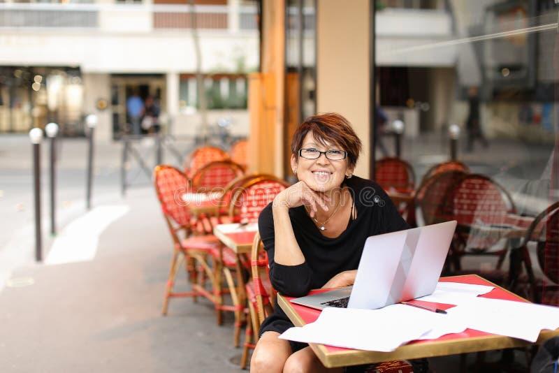 el escritor de sexo femenino envejecido que trabaja con el nuevo libro en ordenador portátil y tiene foto de archivo
