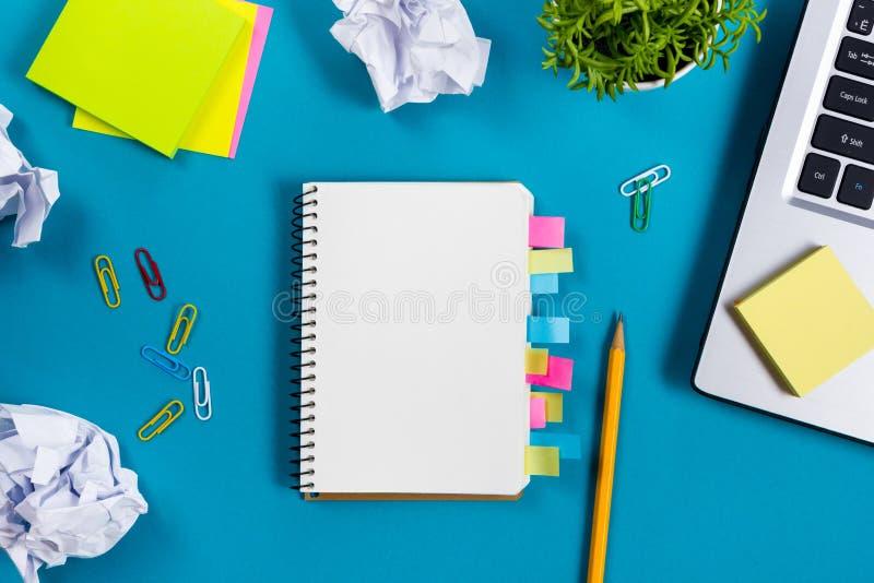 El escritorio de la tabla de la oficina con el sistema de fuentes coloridas, cuaderno de notas en blanco blanco, taza, pluma, PC, imagenes de archivo