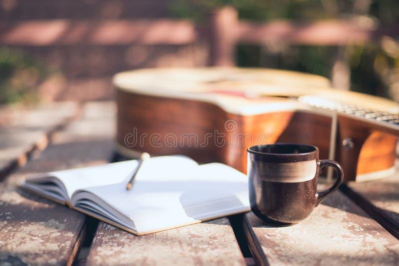 El escritorio del compositor en la naturaleza, taza de café, portátil y guitarra acústica colocada imagenes de archivo