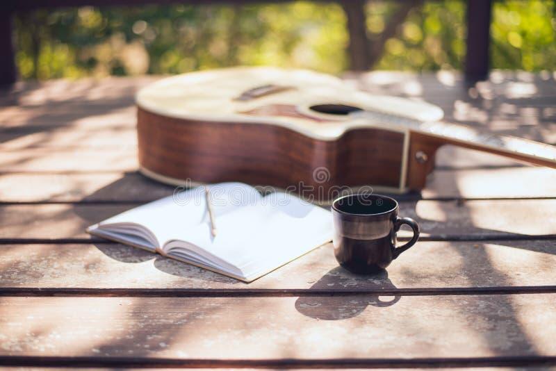 El escritorio del compositor en la naturaleza, taza de café, portátil y guitarra acústica colocada fotografía de archivo
