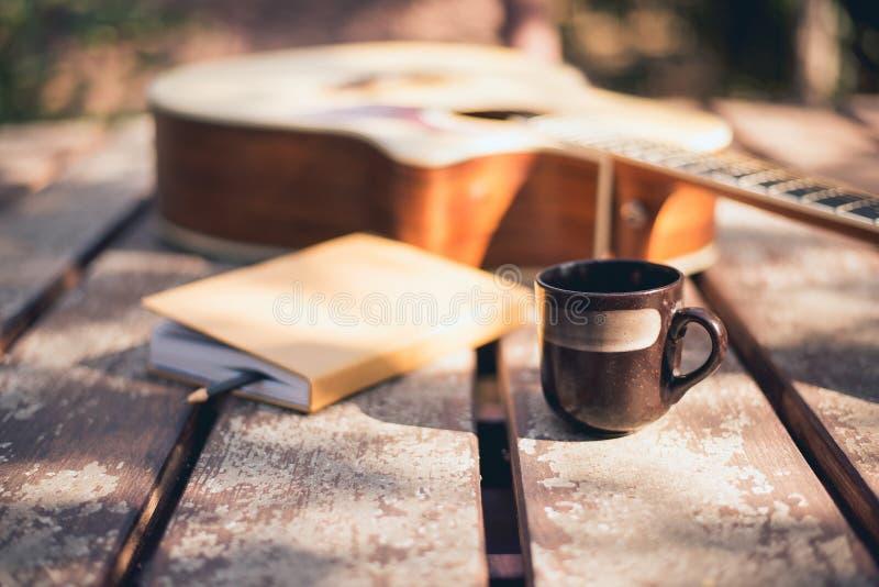 El escritorio del compositor en la naturaleza, taza de café, portátil y guitarra acústica colocada imagen de archivo