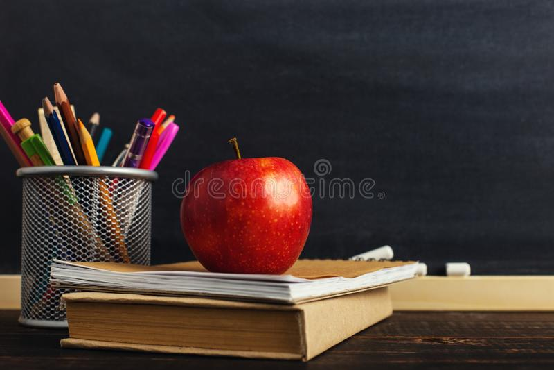 El escritorio del profesor con materiales de escritura, un libro y una manzana, un espacio en blanco para el texto o un fondo par imagenes de archivo