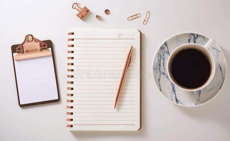 El escritorio puesto plano con el cuaderno, tablero, taza de café y pluma, subió los accesorios del oro fotos de archivo