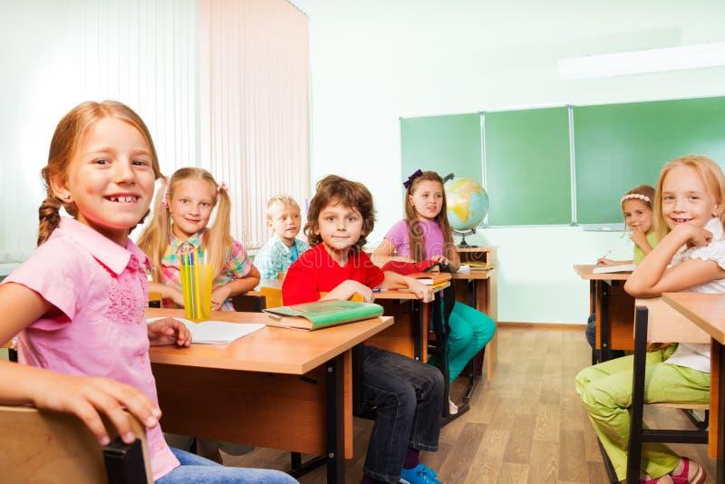 El escritorio rema con los muchachos y las muchachas que se sientan en sala de clase imagen de archivo libre de regalías