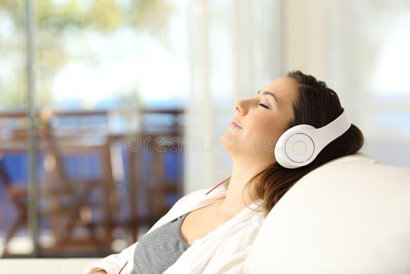 El escuchar de relajación de la mujer la música en un sofá imagenes de archivo