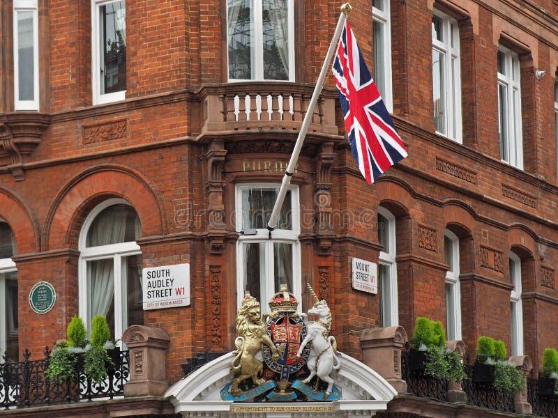 el escudo de armas real aparece en una exhibición patriótica sobre una tienda costosa en Mayfair fotos de archivo libres de regalías