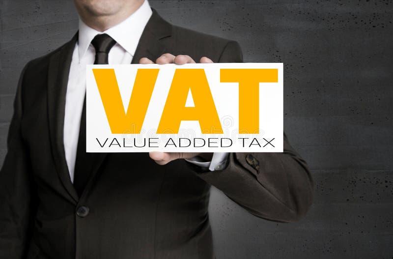 El escudo del IVA es sostenido por el hombre de negocios foto de archivo libre de regalías