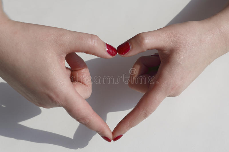 El esmalte de uñas rojo pintado a mano de la mujer de moda, manos hace una forma del corazón imagen de archivo libre de regalías