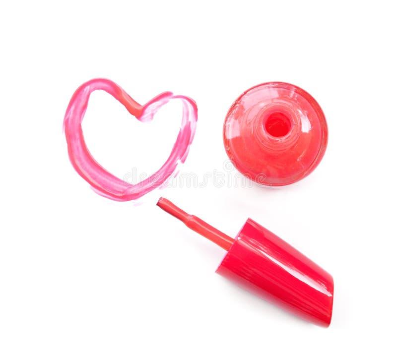 El esmalte de uñas y el cepillo rosados dibujan forma del corazón en el fondo blanco imagen de archivo libre de regalías