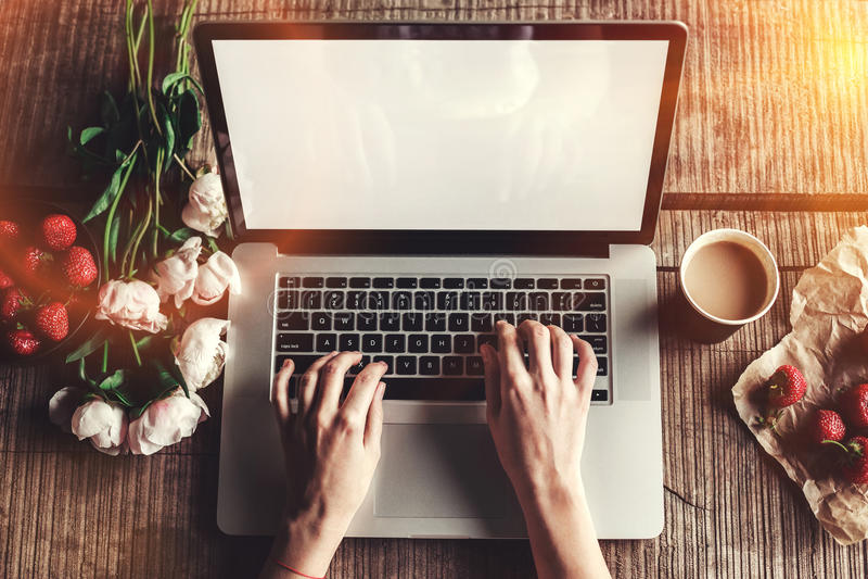 El espacio de trabajo con las manos del ` s de la muchacha, ordenador portátil, ramo de peonías florece, café, fresas, smartphone imagenes de archivo