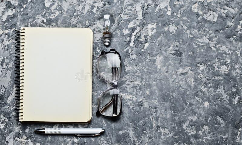 El espacio de trabajo creativo del escritor está inspirando para crear Tengo una idea Libreta, pluma, bulbo incandescente, vidrio imagenes de archivo