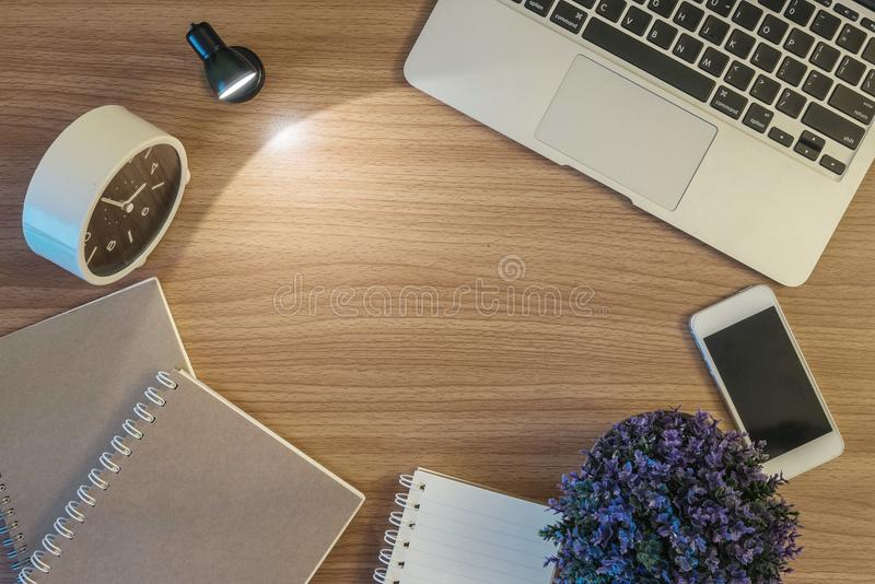 El espacio del primer del escritorio de madera marrón con la luz de la pequeña lámpara en el cuarto oscuro con el libro borroso d fotos de archivo