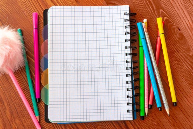 El espacio en blanco ajustó el cuaderno con las plumas y los lápices de la extremidad sentida coloridas en el escritorio de mader imagen de archivo