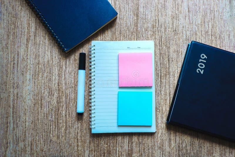 El espacio en blanco de la visión superior de la nota del poste y el cuaderno adornan con la pluma y el libro stock de ilustración