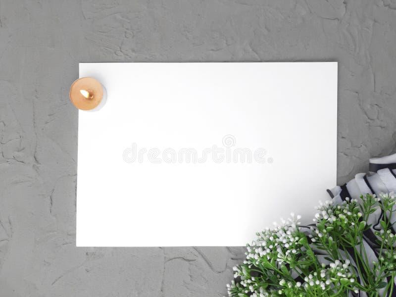 El espacio en blanco vacío con las flores ramifica, quemando la vela y la bufanda en fondo gris fotos de archivo