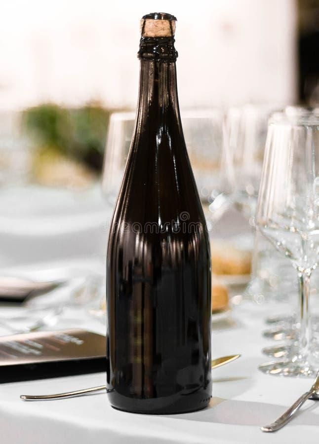 El espacio oscuro del blanck de la botella de cristal de la sidra del champán del vino en tabla de lujo fijó en la celebración de imagen de archivo libre de regalías