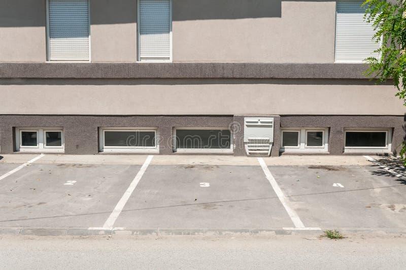 El espacio privado del estacionamiento para los coches con la reserva numera delante del edificio residencial en la ciudad imágenes de archivo libres de regalías