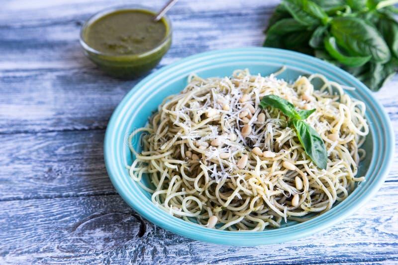 El espagueti de las pastas con la salsa y la albahaca hechas en casa del pesto hojea, madera foto de archivo