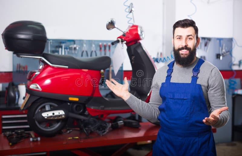 El especialista de la reparación de la motocicleta muestra su lugar de trabajo fotografía de archivo libre de regalías