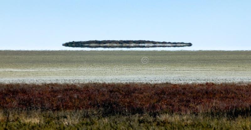 El espejismo del espejismo parece el UFO sobre el desierto foto de archivo