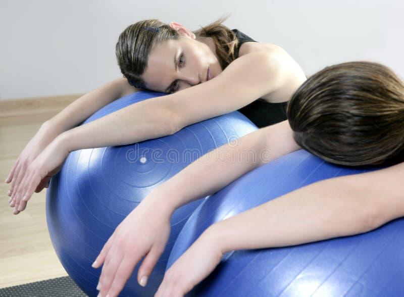 El espejo de los aeróbicos relaja la bola de la estabilidad de los pilates de la mujer imagenes de archivo
