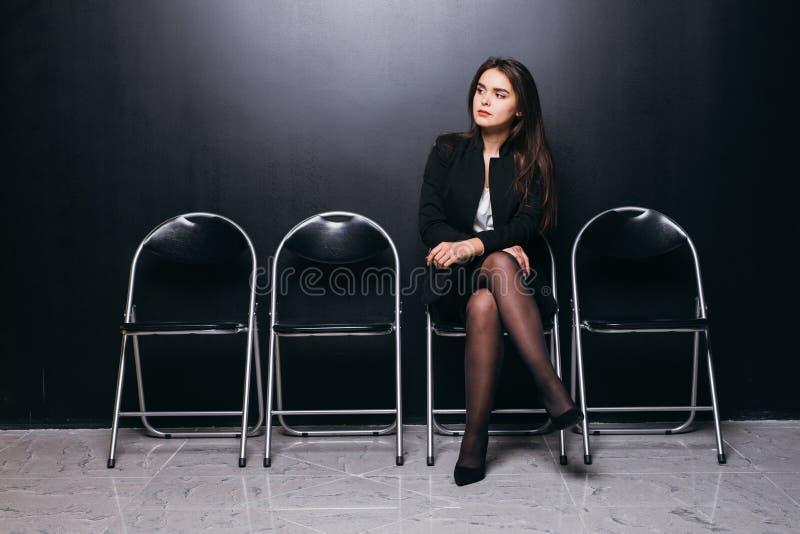 El esperar en línea Empresaria joven confiada que se sienta en silla contra fondo negro fotos de archivo