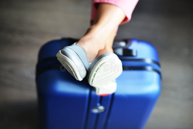 El esperar hermoso de la mujer retrasado o vuelo de la conexión con equipaje en aeropuerto imagen de archivo