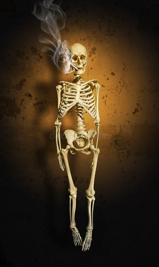El esqueleto de un hombre con un cigarrillo que fuma contra la pared foto de archivo