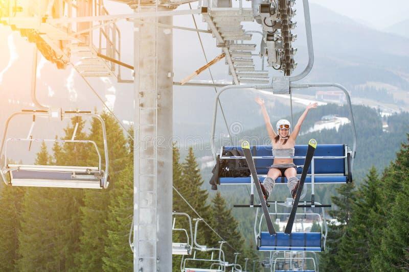 El esquiador atractivo de sexo femenino feliz se está incorporando en el remonte, mano de levantamiento y está montando hasta el  fotos de archivo