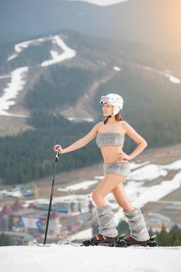 El esquiador de sexo femenino atractivo joven está presentando en el top de la cuesta con los esquís Botas, casco y gafas de sol  imagen de archivo libre de regalías