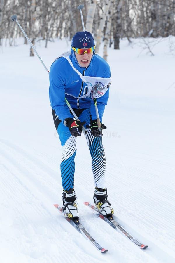 El esquiador de sexo masculino en traje azul de los deportes está montando de la montaña en los esquís en bosque del invierno imagen de archivo libre de regalías