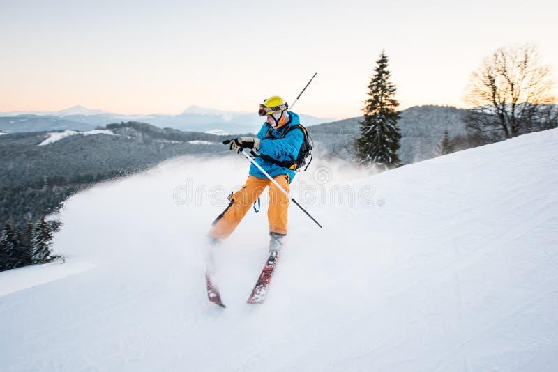 El esquiador en polvo de la nieve produce el frenado en la cuesta de la montaña imagen de archivo